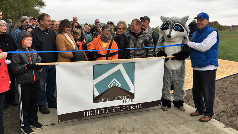 Young Tate Boyd and the Raccoon River Valley Trail's mascot at the ribbon-cutting ceremony.